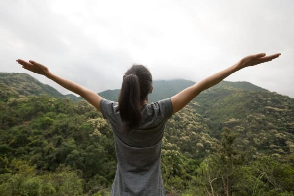 Woman with arms outstretched overlooking beautiful view of mountains